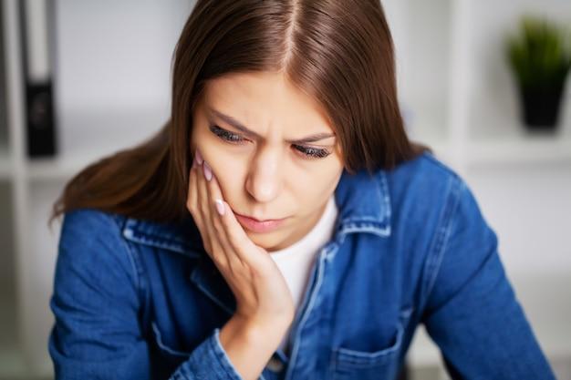 激しい歯痛で苦しんでいるオフィスで疲れきった女性