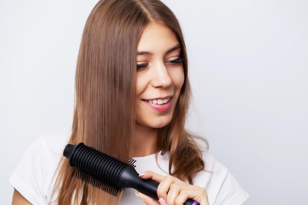 美しい若い女性はストレートヘアアイロンを使用して美しいスタイリングを作る