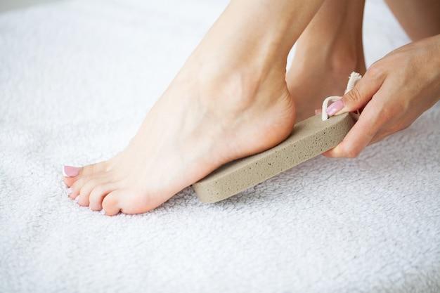 Женщина чистит пятку стопы с помощью пемзы