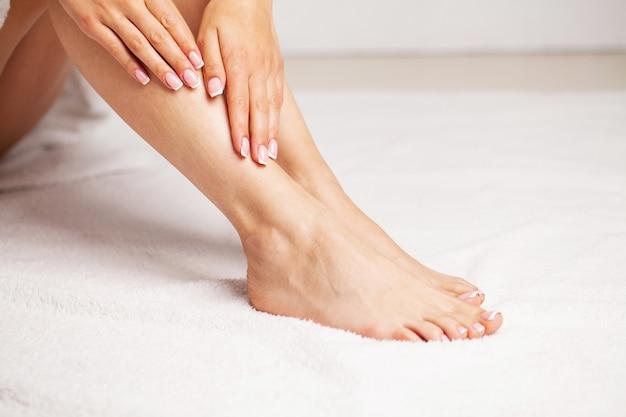 美しい滑らかな肌、レッグケアのコンセプト、脱毛機能を持つ女性の長い脚