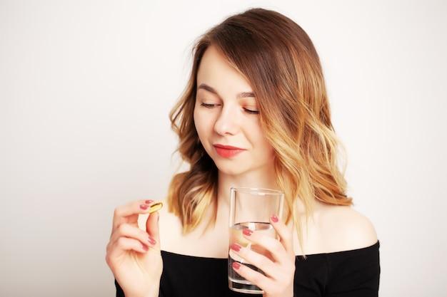 Счастливая улыбающаяся положительная женщина ест таблетку и держит стакан воды в руке, в своем доме