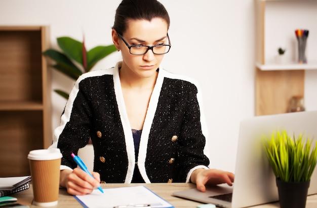 Исчерпаны деловая женщина работает в офисе на ноутбуке