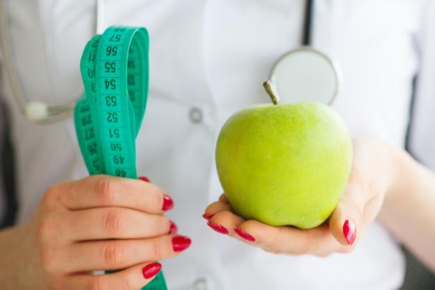 女性栄養士とリンゴとメジャーテープを保持しています。健康的な栄養、ボディスリミング、減量のための新たなスタート。体を気にする
