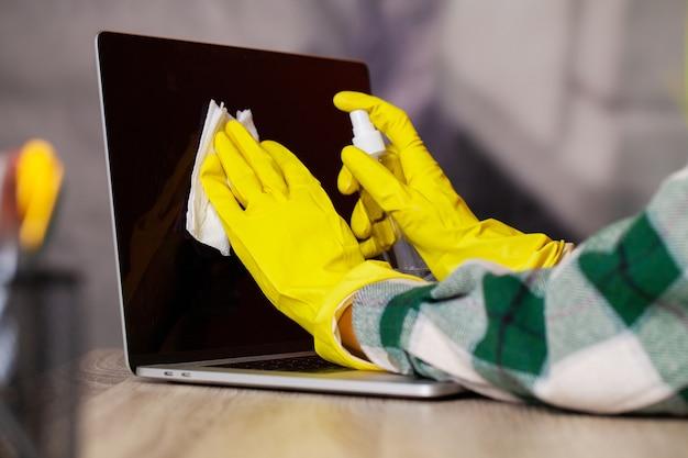 Женщина вытирает ноутбук от пыли в офисе за столом
