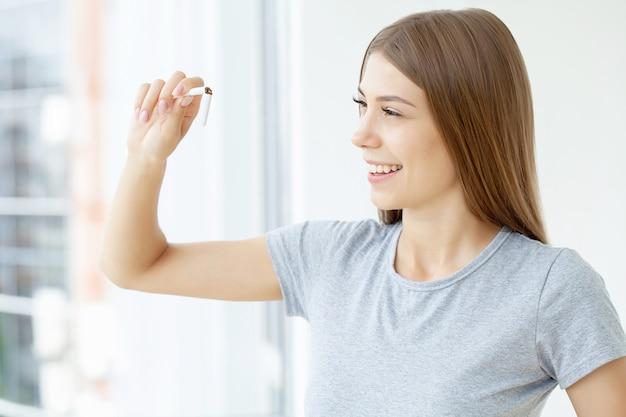 喫煙をやめる、壊れたタバコを手に持った女性