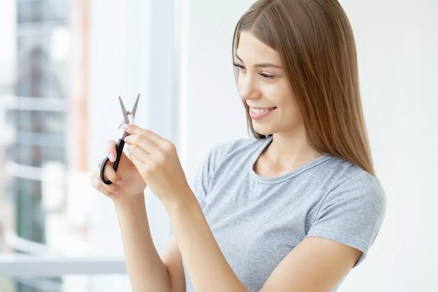 喫煙をやめる、女性はハサミでタバコを切る