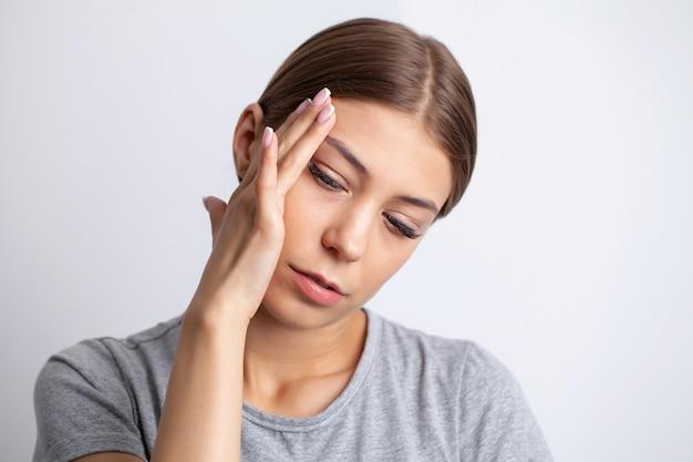 若い女性は激しい頭痛を持っています