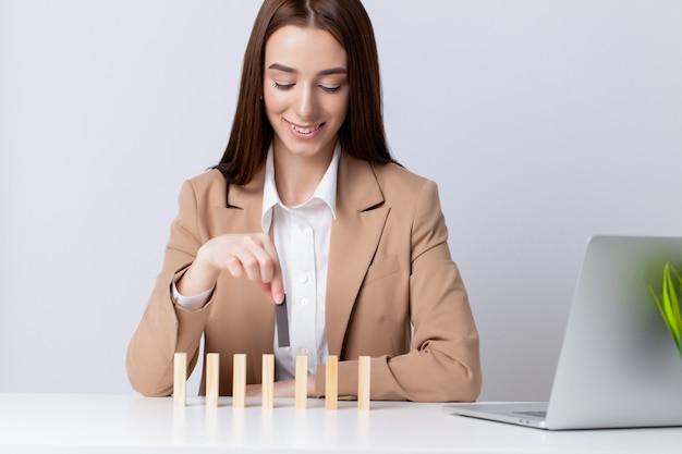 美しい若い女性はオフィスの机の上の木製キューブになります