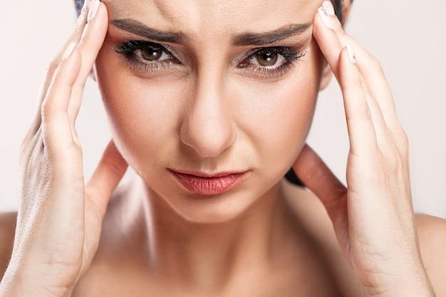 頭痛に苦しんで美しい病気の女の子のクローズアップの肖像画