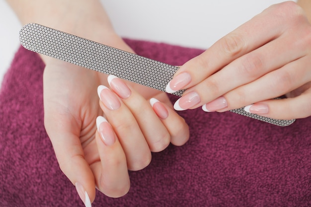 ビューティーサロンでのスパマニキュアを持つ美しい女性の手のクローズアップ。美容師ファイリングクライアント爪やすりで健康的な天然の爪。