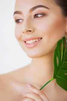 スパケア大きな緑の葉を持つ若いかなりブルネットの女性