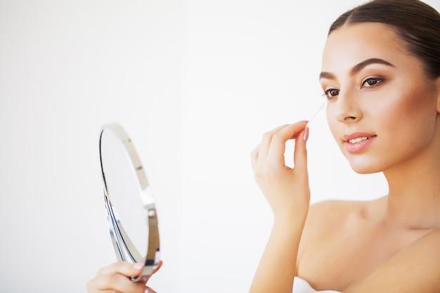 スキンケア。室内の鏡で見ている新鮮な健康的な肌を持つセクシーな若い女性の肖像画