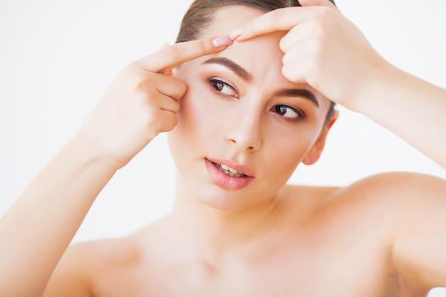 問題のある肌。女性の顔にスポットを押しつぶし、鏡で見ている