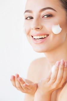 美容フェイスケア。顔の肌にクリームを持つ女性