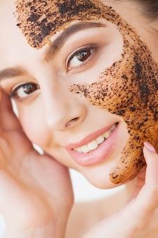 フェイススキンケア若い魅力的な女の子は彼女の顔に黒い木炭マスクを作ります