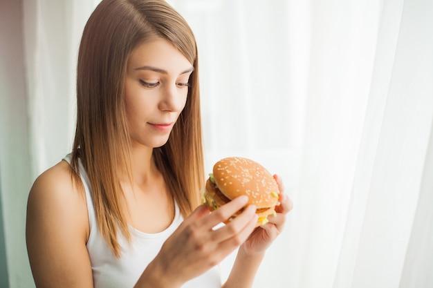 健康的な食事のコンセプト、ジャンクフードを食べることを防ぐ彼女の口の上のダクトテープを持つ若い女