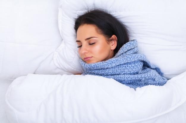 毛布の下で横になっている風邪を持つ少女