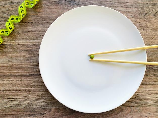 白い皿の上の画像のエンドウ豆のトリミング、フォークと測定
