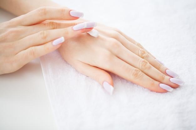 完璧なマニキュアで美しい女性の手が肌の手にクリームを適用します、