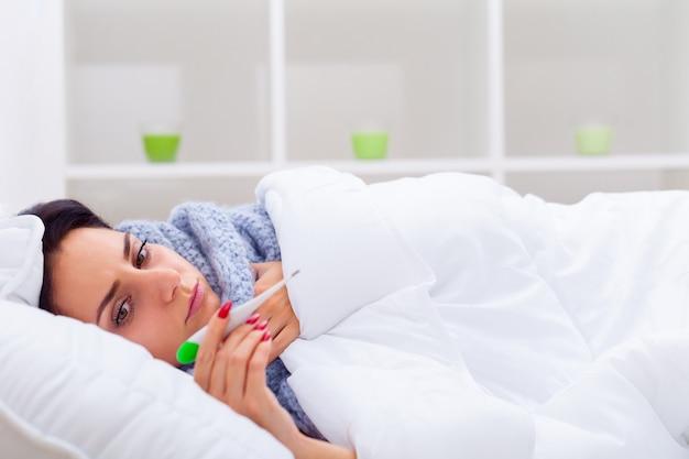 若い女性の手で押しながらベッドに横たわっている間温度計を見て