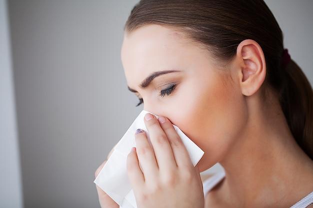 インフルエンザと病気の女性。ティッシュペーパー、頭の冷たい問題を使用して病気の女性