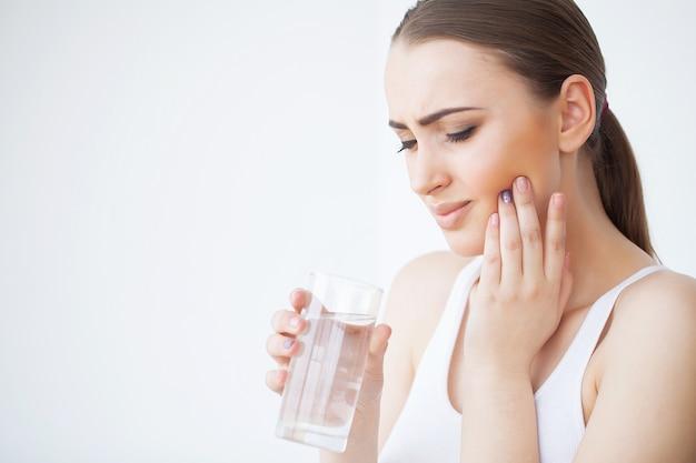 歯痛。美しい女性の強い痛みを感じて