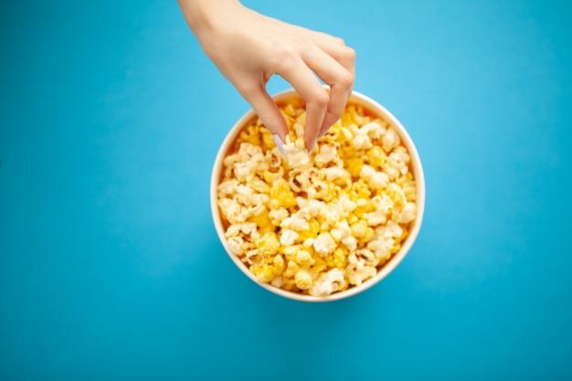 Продукты питания. женская рука, которая берет попкорн из ведра. ведро для попкорна. кино