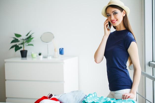 Женщина, которая готовится к отдыху. молодая красивая девушка сидит на кровати. портрет улыбающейся женщины.
