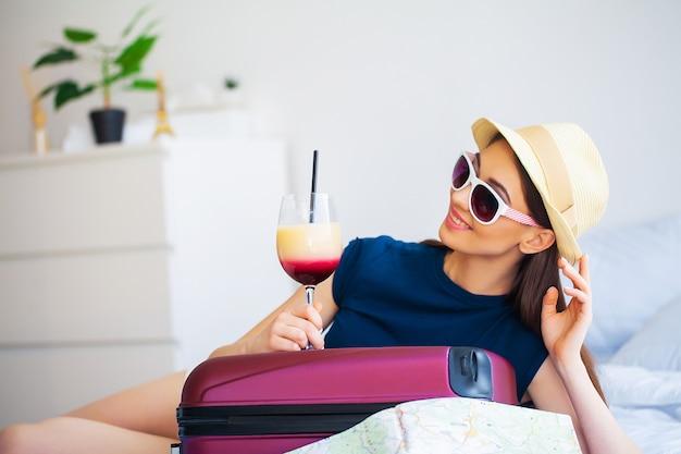 カクテルと、ズボンの部屋でベッドの上のスーツケースを持つ美しい女性