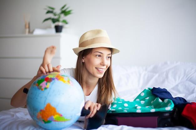 休暇休息の準備をしている女性。美しい少女はベッドの上に座っています。笑顔の女性の肖像画。幸せな女の子が休暇に入ります