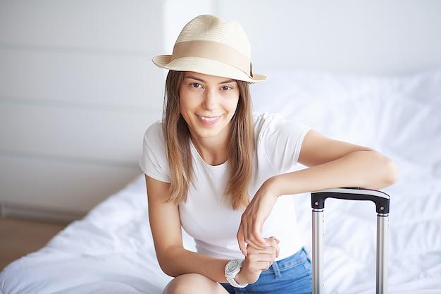 女性の足が手荷物、自宅で若い女性がベッドに敷設を引き上げた。白い寝室