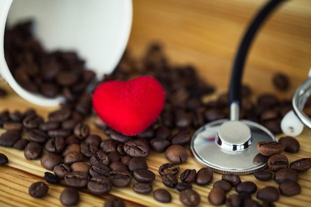 おはようございます。木製のテーブルの上のコーヒー豆と紙のコーヒーカップ