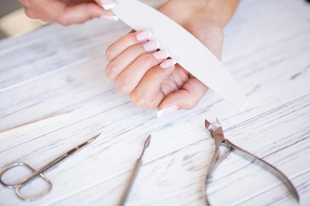 女性ハンドケア。ビューティーサロンでのスパマニキュアを持つ美しい女性の手のクローズアップ。美容師ファイリングクライアント爪やすりで健康的な天然の爪。ネイルトリートメント