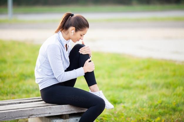 足のけが。トレーニング後の脚の痛みに苦しんでいる女性