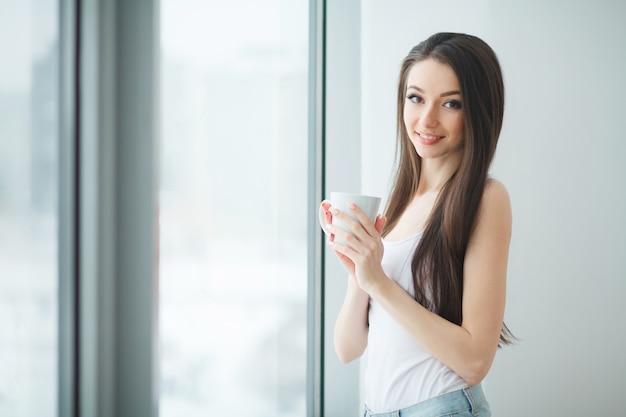 屋内で明るい近代的なオフィスで一杯のコーヒーを持つ若いかなりビジネス女性