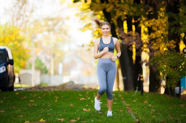 フィットネス、美しい若い女性は公園でのエクササイズ