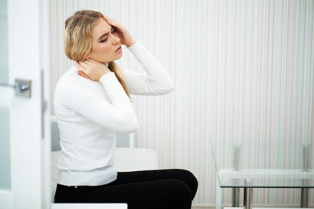 美しい若い女性は気分が悪く、首に痛みがあります