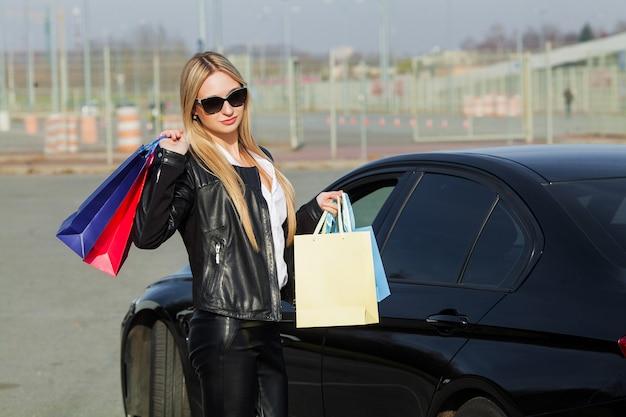 黒い金曜日の休日に彼女の車の近くの色の袋を保持している女性