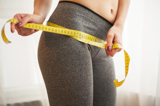 手をテープで腰を測定します。彼女の家でスリムで健康的な女性