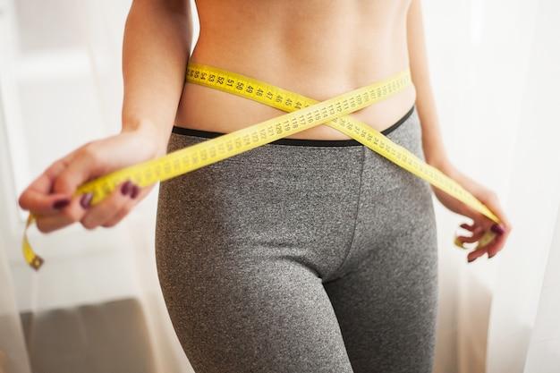 Руки измеряют талию скотчем. стройная и здоровая женщина у себя дома