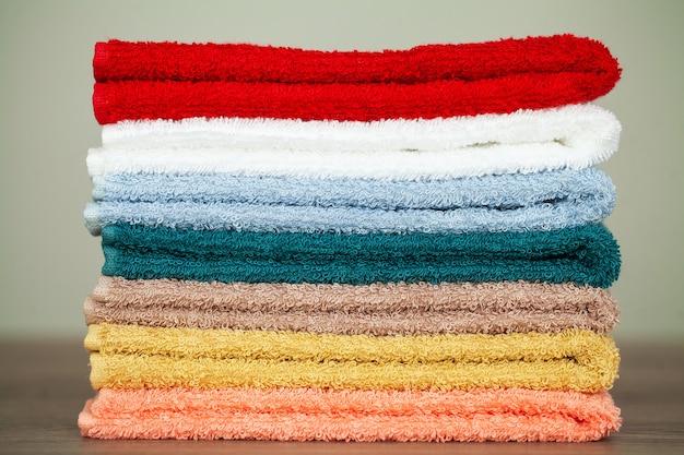 テーブルの上のバスルームにカラフルなタオルを積み重ねる