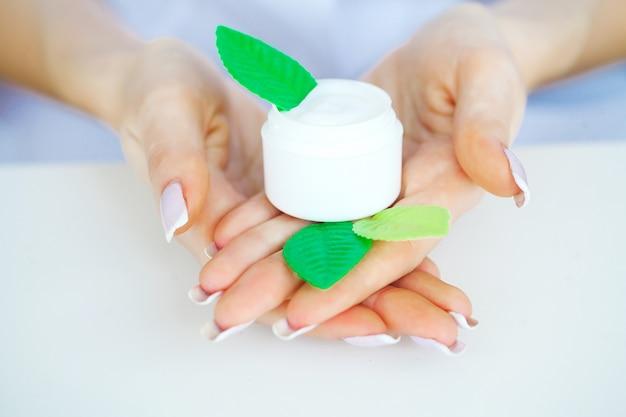 女性ハンドクリーム。クリームや治療用軟膏で手のクローズアップ