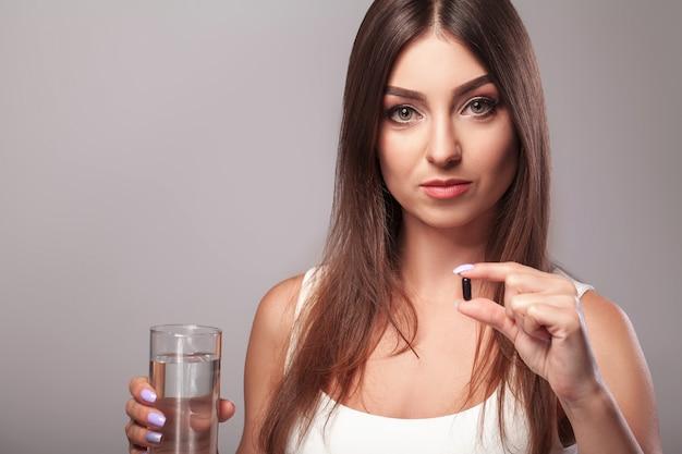 風邪やインフルエンザ。水のガラスを保持しているとカプセルを取っている女性