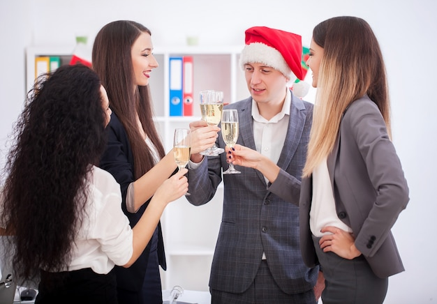 Счастливые деловые люди в шляпах санта смотрят на камеру и улыбаются во время празднования нового года