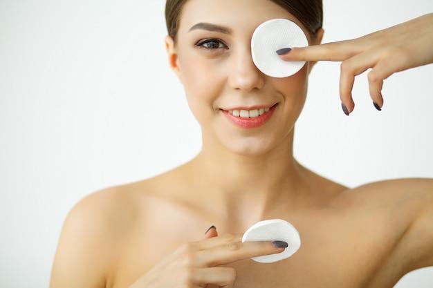 スキンケア。バスルームで顔を洗うローションを持つ若い女