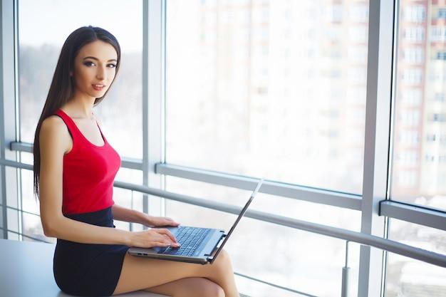 Молодая женщина работает на ноутбуке в офисе