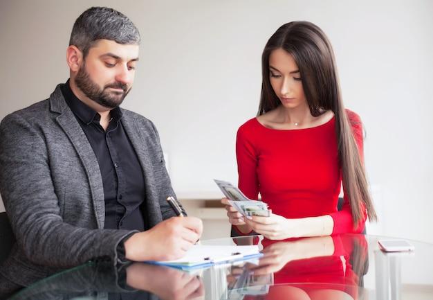 ビジネス。ビジネスの女性は男性にお金を与えます。