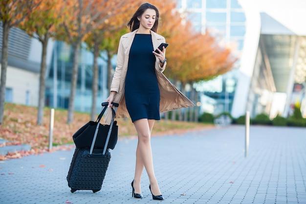 空港コンコースを通してスーツケースを引いてゲートを出るために進んでいる女性の乗客の笑顔