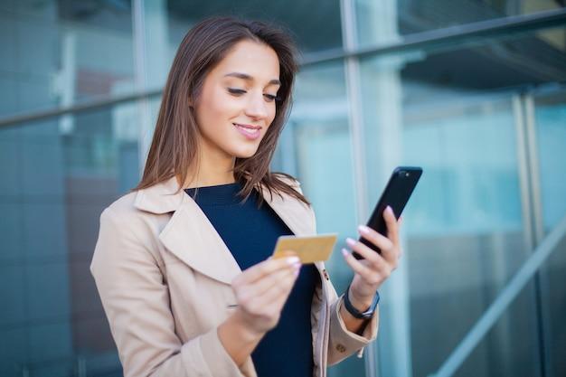 空港ホールに立っている満足している女の子のローアングル。彼は支払いにゴールドのクレジットカードと携帯電話を使っています