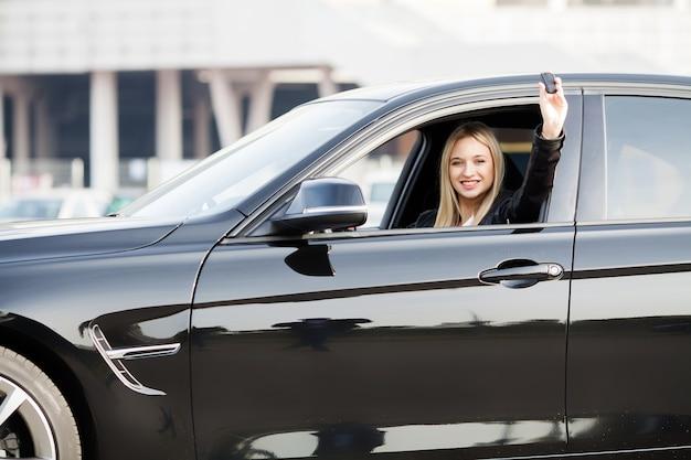 彼女の新しい車に立地の車のキーを保持している女性ドライバー